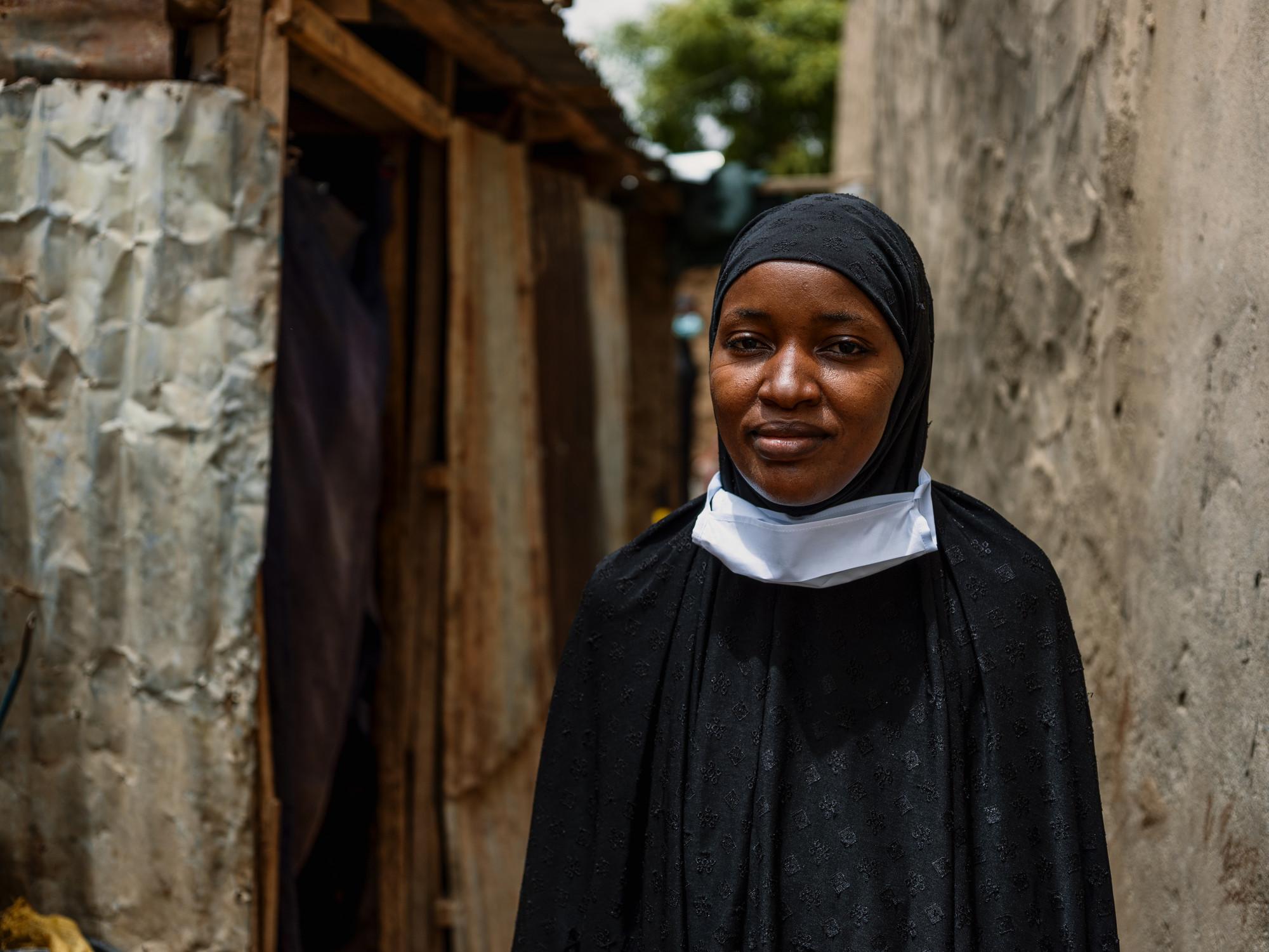 Uma mulher no Níger está parada entre uma parede de concreto e uma casa feita de metal corrugado e madeira.