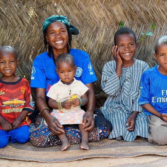 Uma mãe se senta em um tapete com quatro de seus filhos em frente a uma parede de tecido no Níger.