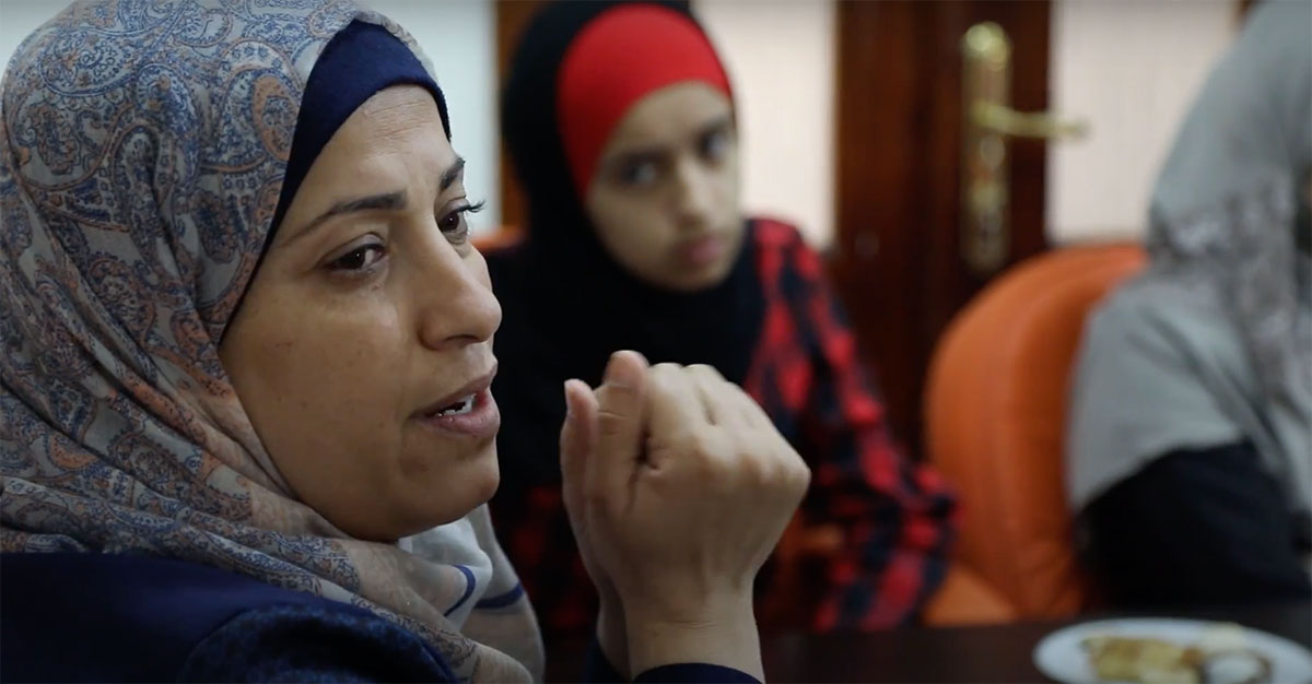 A close-up image of a woman wearing a head scarf speaks to a small group of people.