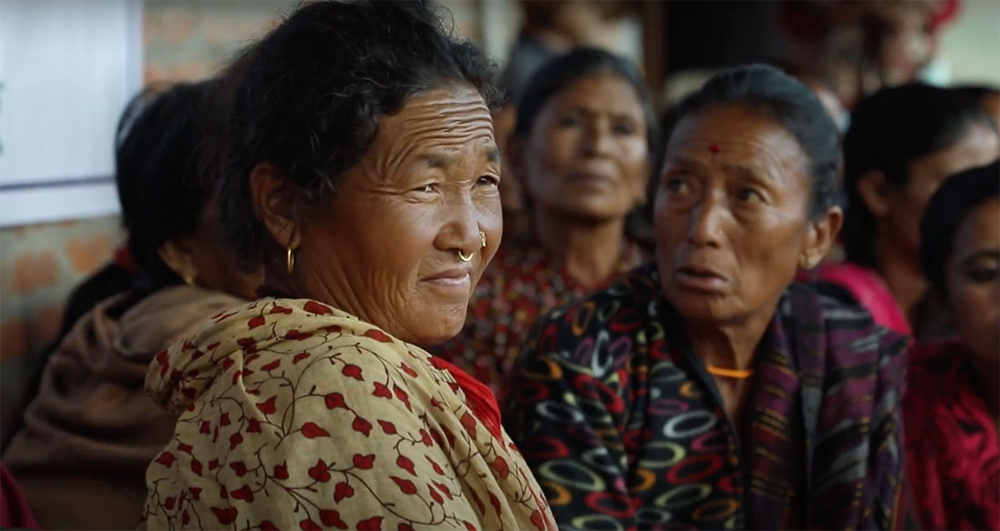 A middle-aged woman in a group of Nepali women.