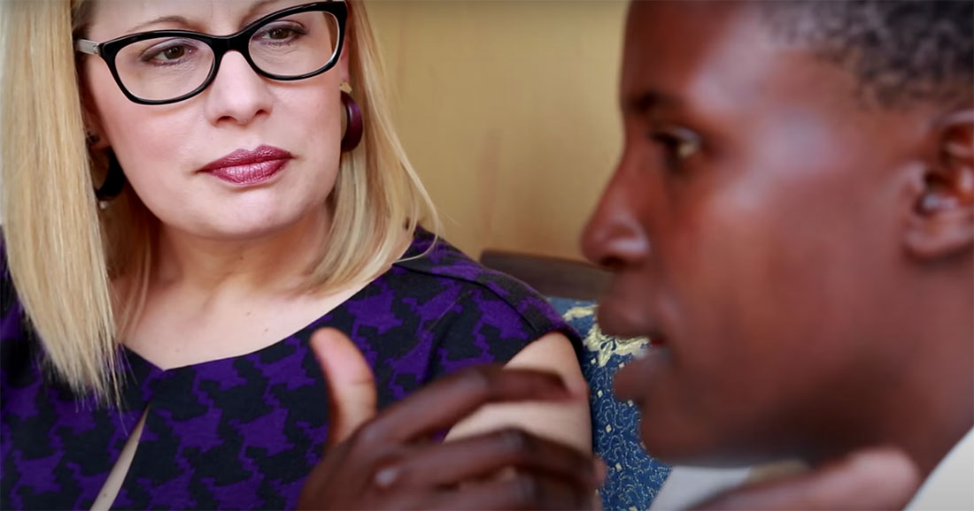 A woman wearing glasses listens to a young girl speak.