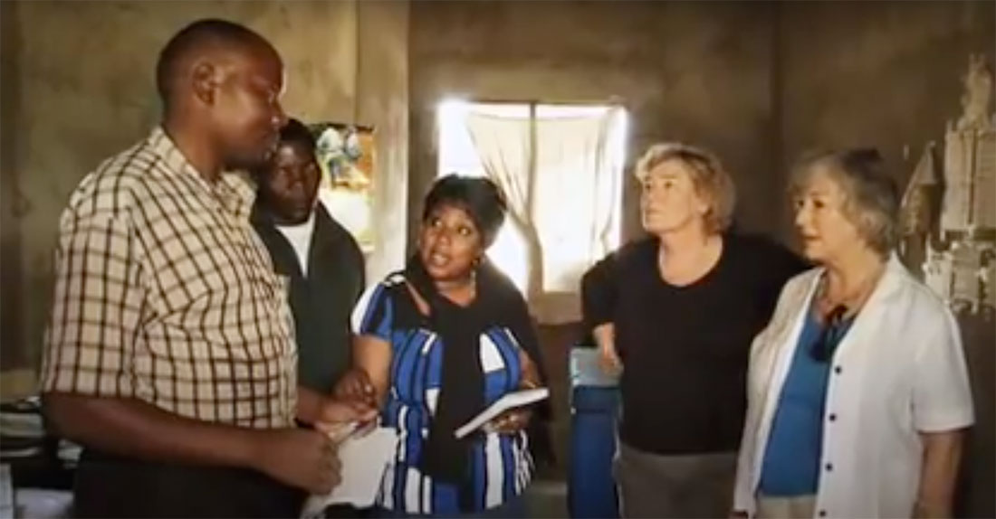 A man holding a notebook speaks with a group of women.