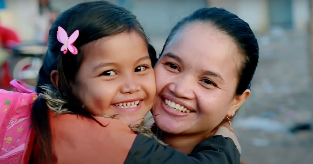A woman and child hold each other close and smile.