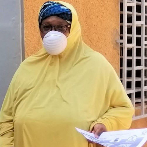 A woman in yellow with a mask on stands in front of a wooden door in Niger while holding papers.