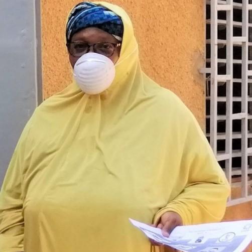 Uma mulher vestida de amarelo com uma máscara fica em frente a uma porta de madeira no Níger, segurando papéis.