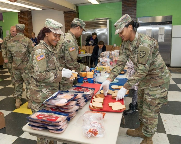 Members of the Army National Guard and other volunteers prepare bags of food for residents of New Rochelle, New York, where a one-mile radius containment area was set up to halt the spread of coronavirus. (Shutterstock)