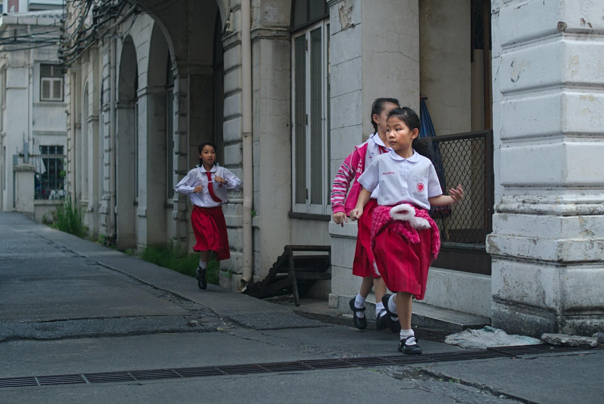 Três colegiais tailandesas uniformizadas caminham na calçada em frente a um prédio cinza com colunas.