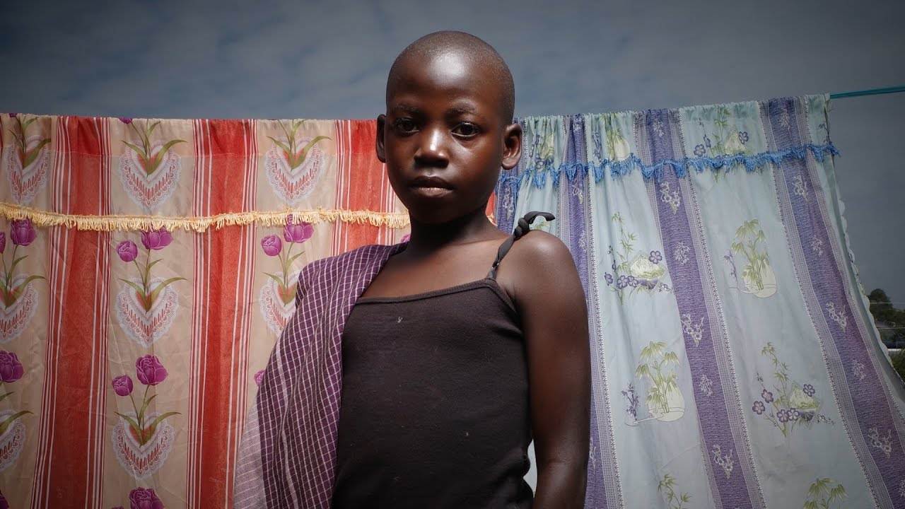 A young girl stands in front of two pieces of fabric hung on a string.