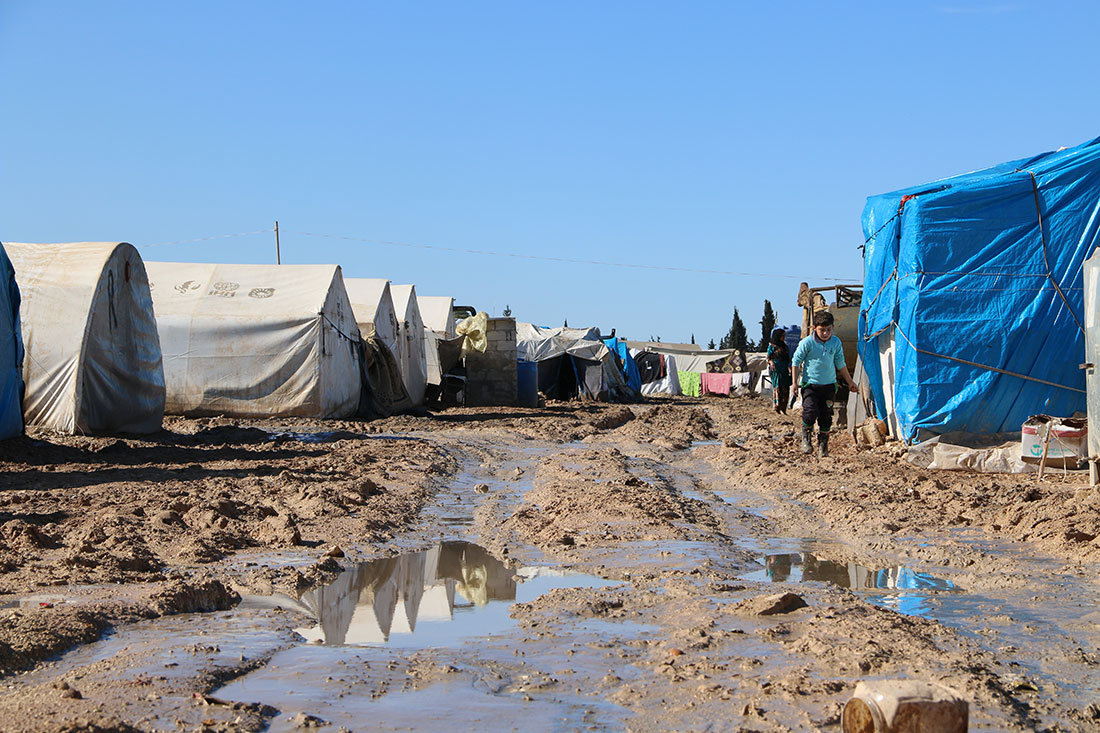 A landscape photo of a refugee camp in Syria. There are multiple large white tents lining a muddy street.
