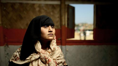 A woman wearing a black head scarf looks to the side while sitting in a house. Behind her, a small town is visible through an open window.