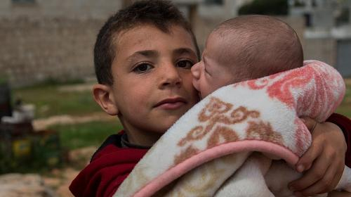 A boy, displaced from Aleppo, clutches his cousin. He and his family nowlivein a camp in Idlib, in northwestern Syria. CREDIT:Syria Relief/CARE