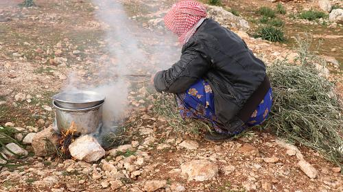 A displaced Syrian woman builds a stone stove to cook for her family and uses the branches of live trees to light the fire.