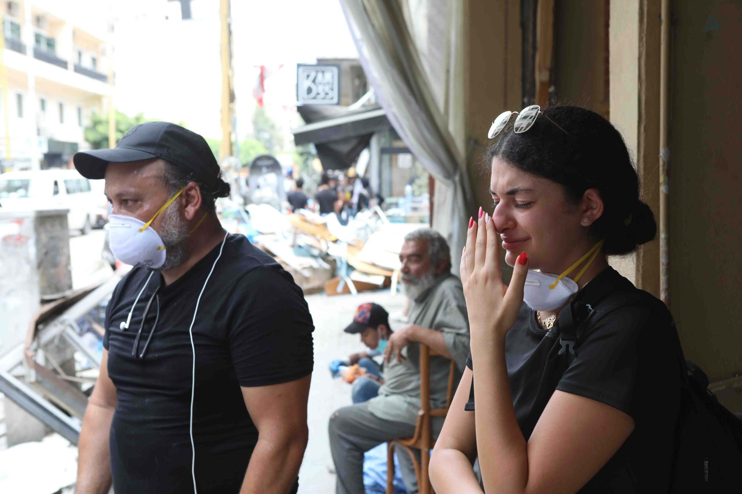 A man in a mask and a crying young woman with sunglasses on her head and a mask around her neck look at wrecked streets and buildings in Beirut.