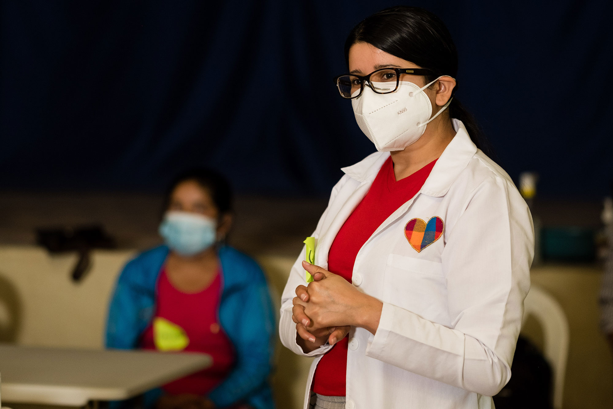 a woman in a lab coat and surgical mask stands.