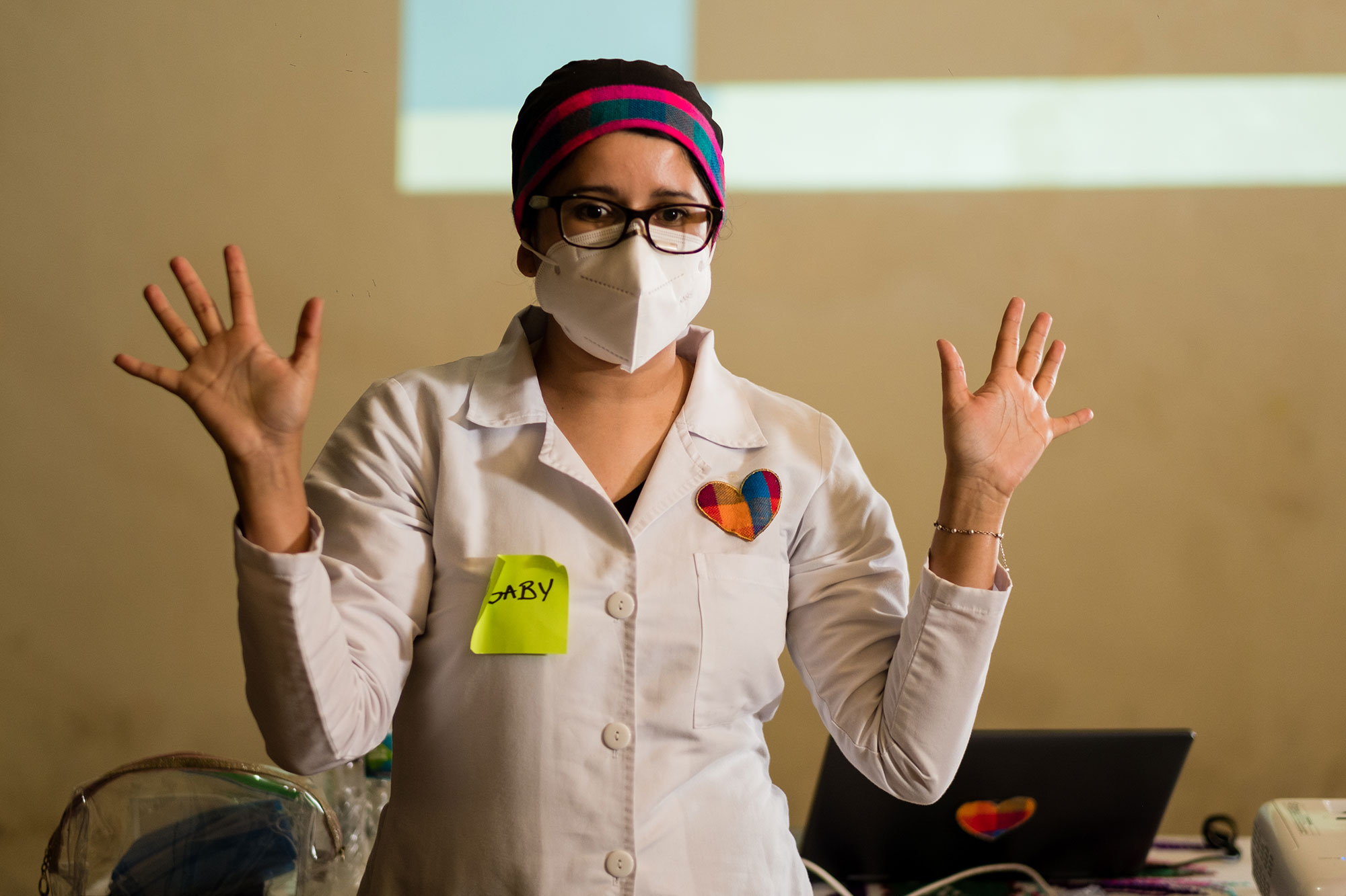 a woman in a lab coat and surgical mask talks with bother her hands up in the air.