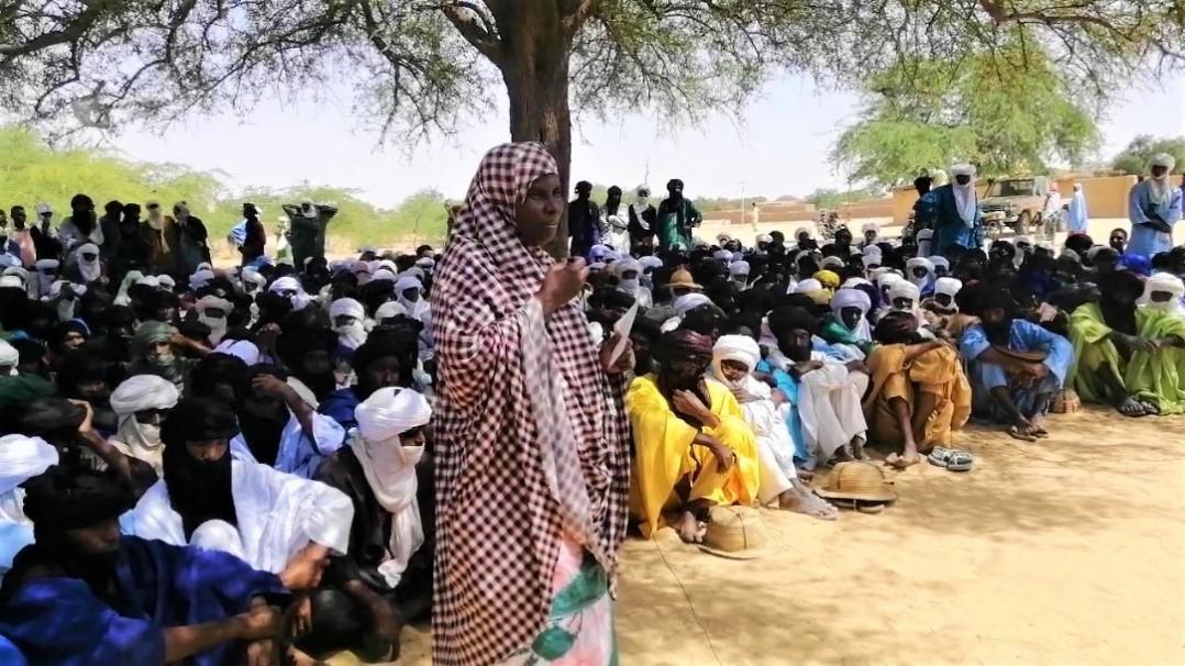 Uma mulher com uma bandagem xadrez está diante de uma multidão de mulheres sentadas.