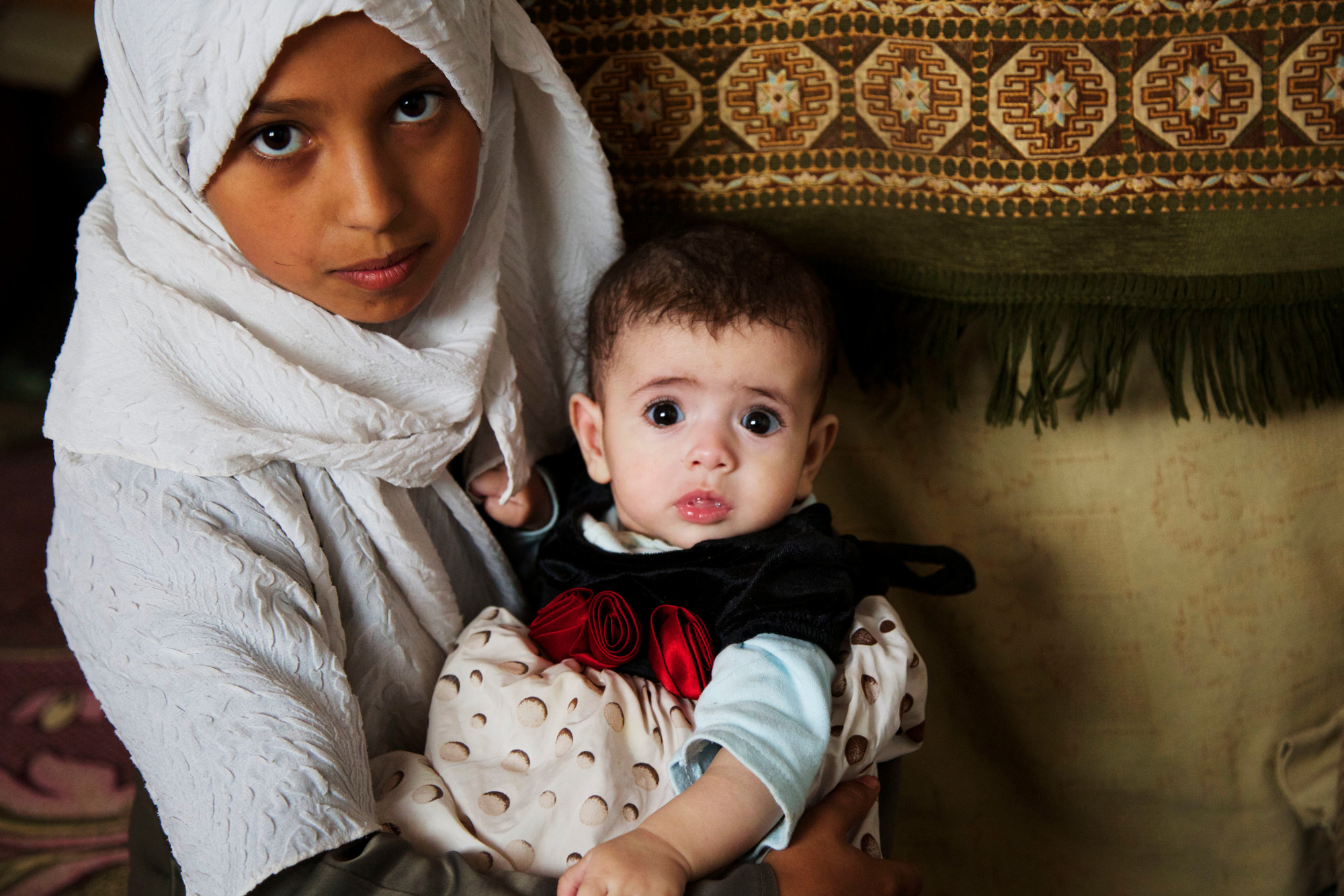 A woman holds a baby in her arms.