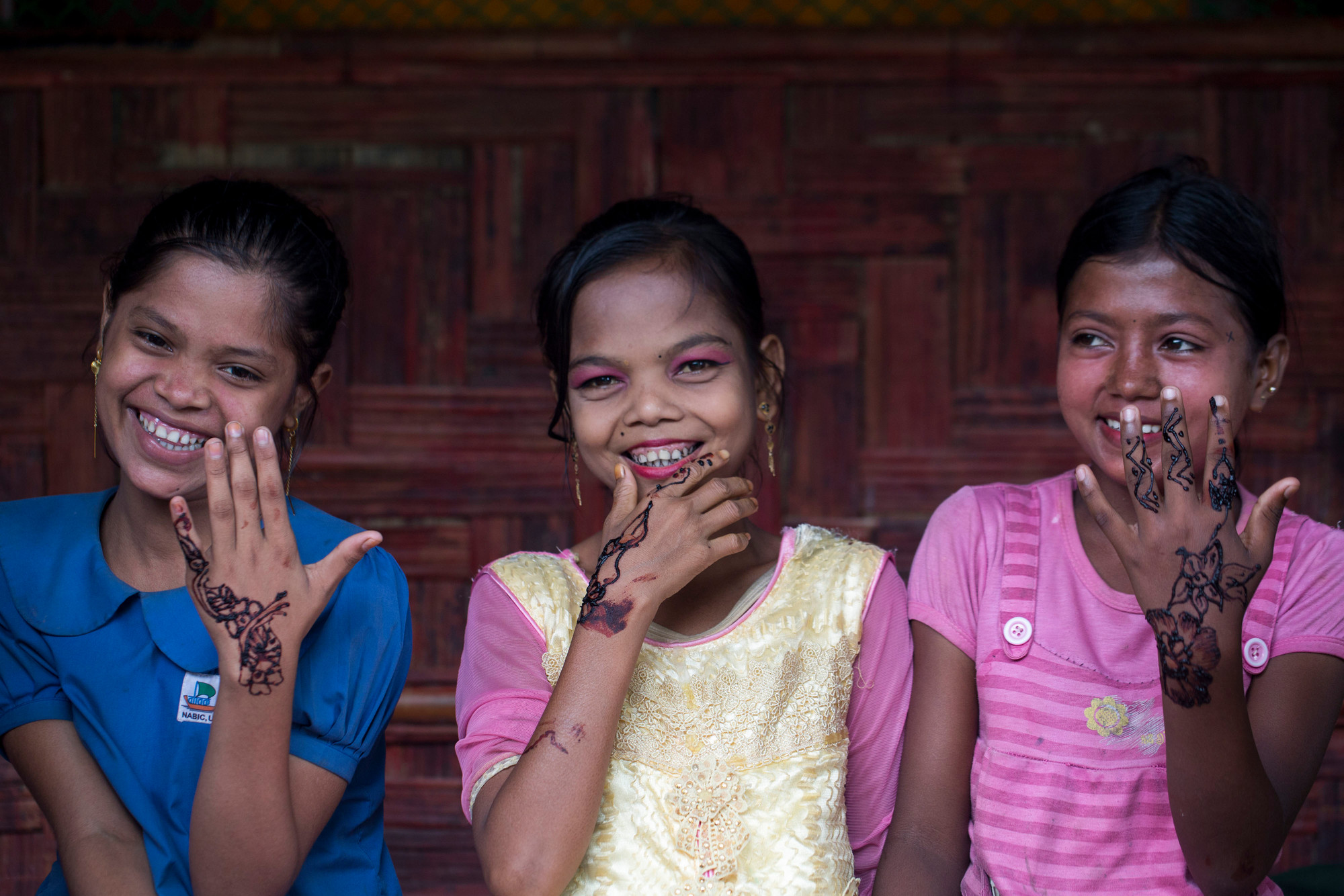 Three girls smile while displaying traditional decorations drawn on their hands.