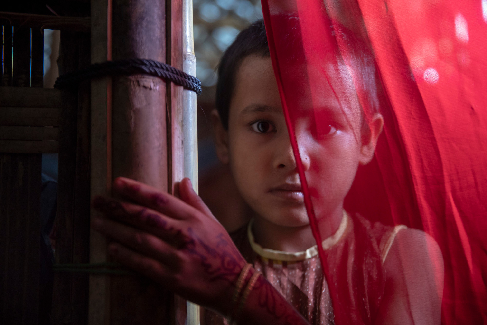 A girl in a temporary shelter looks forward while a piece of red fabric obscures half of her face.