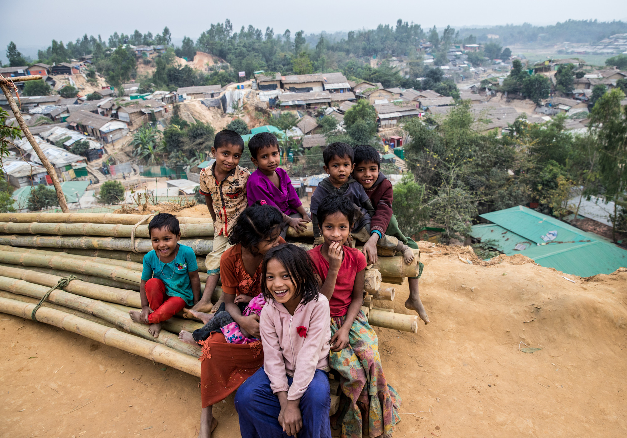 A group of children smile while sitting on a pile of large bamboo poles arranged in bundles.