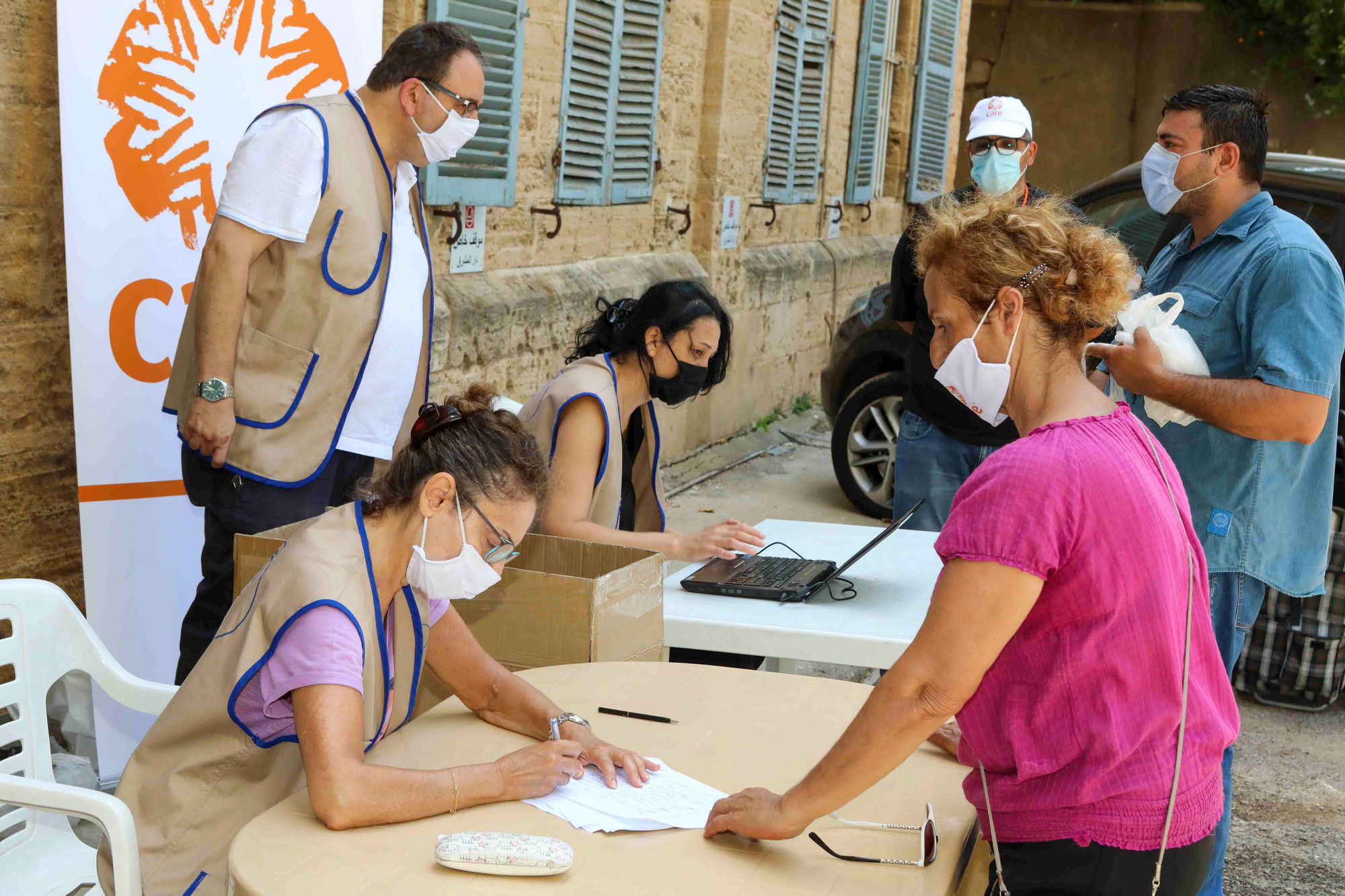 A woman worker in a mask fills out a form at a food distribution site in Beirut while another woman in a mask stands across the table from her.