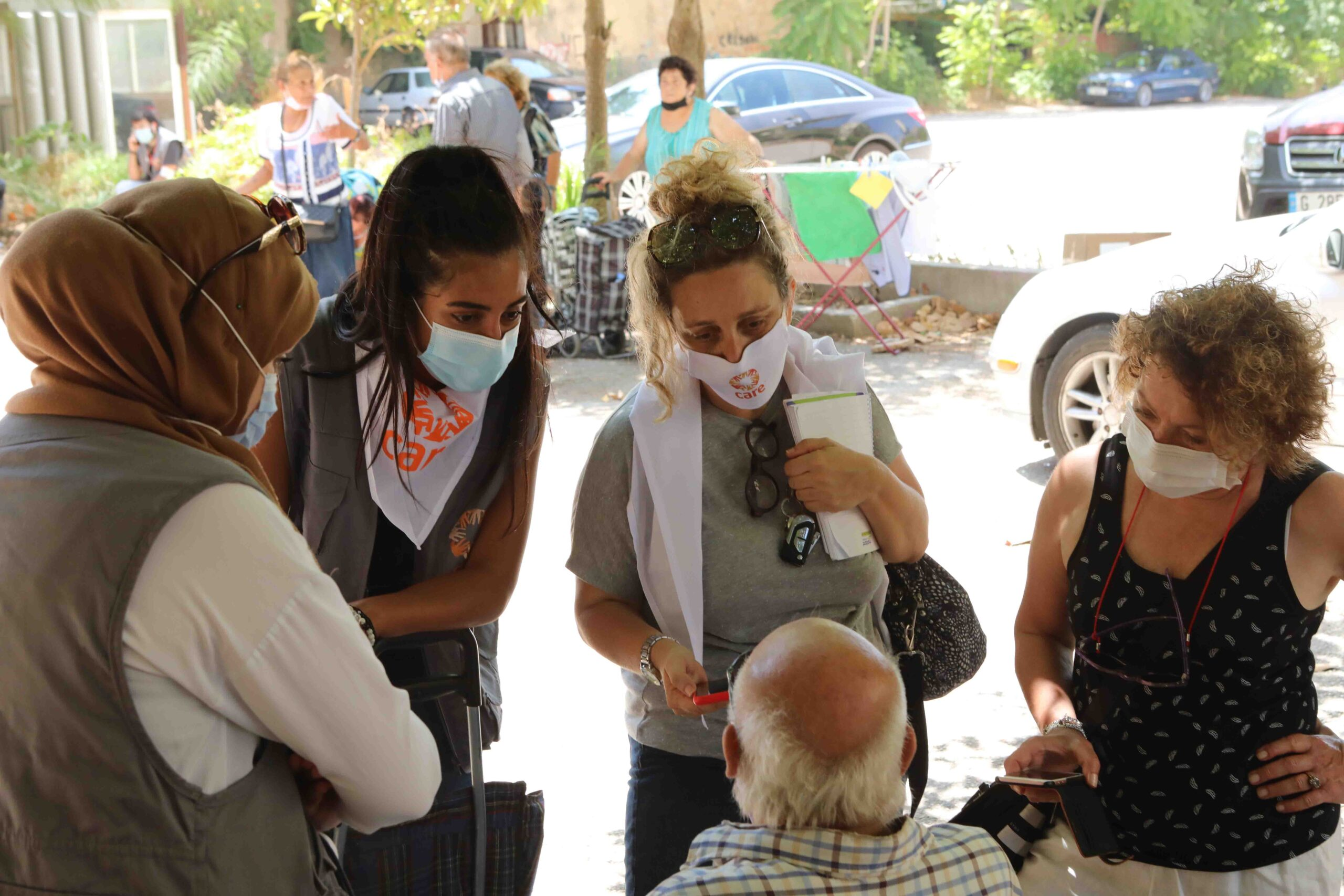 Four women in CARE face mask speak to a seated man.