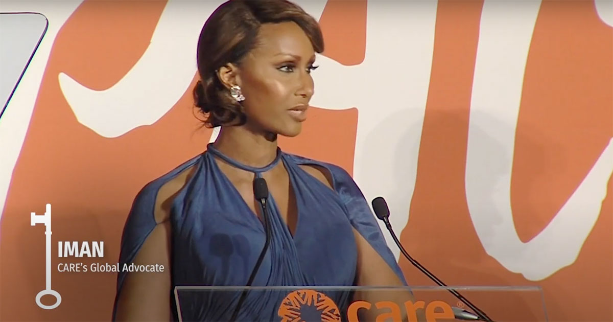 Iman wears a royal blue gown while accepting an award. She is speaking at a pedestal decorated with a CARE logo.