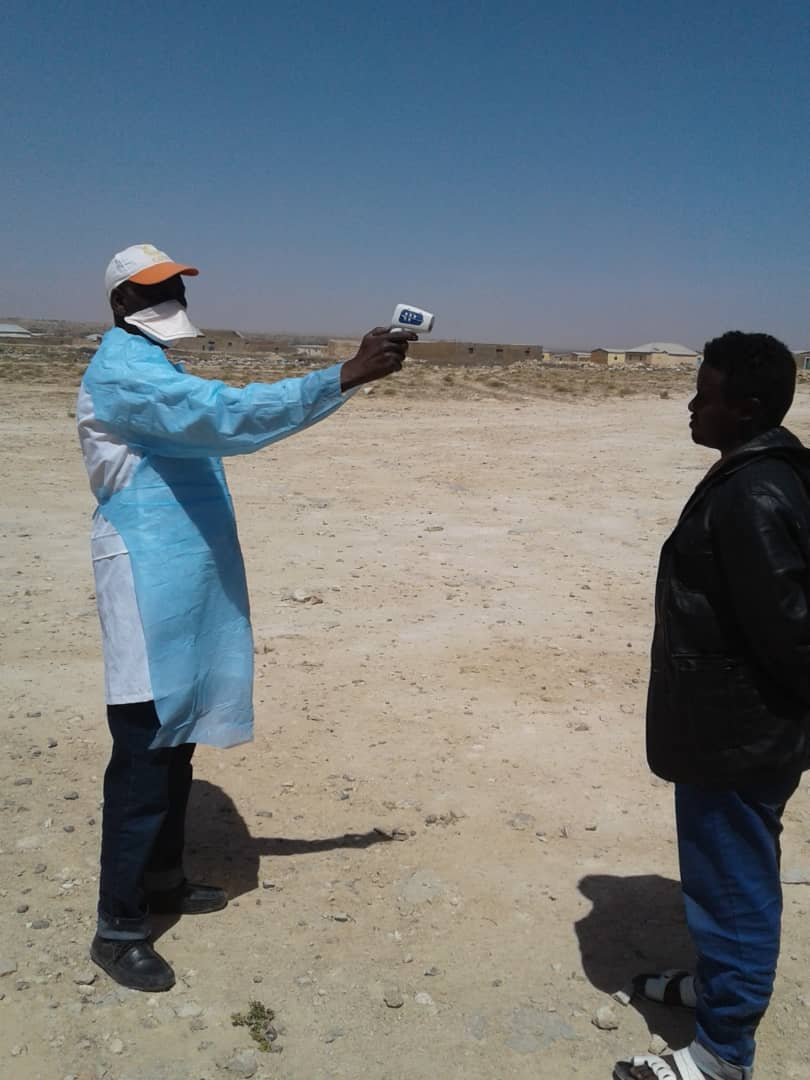 A man in surgical mask takes the another person's temperature with an infrared thermometer.