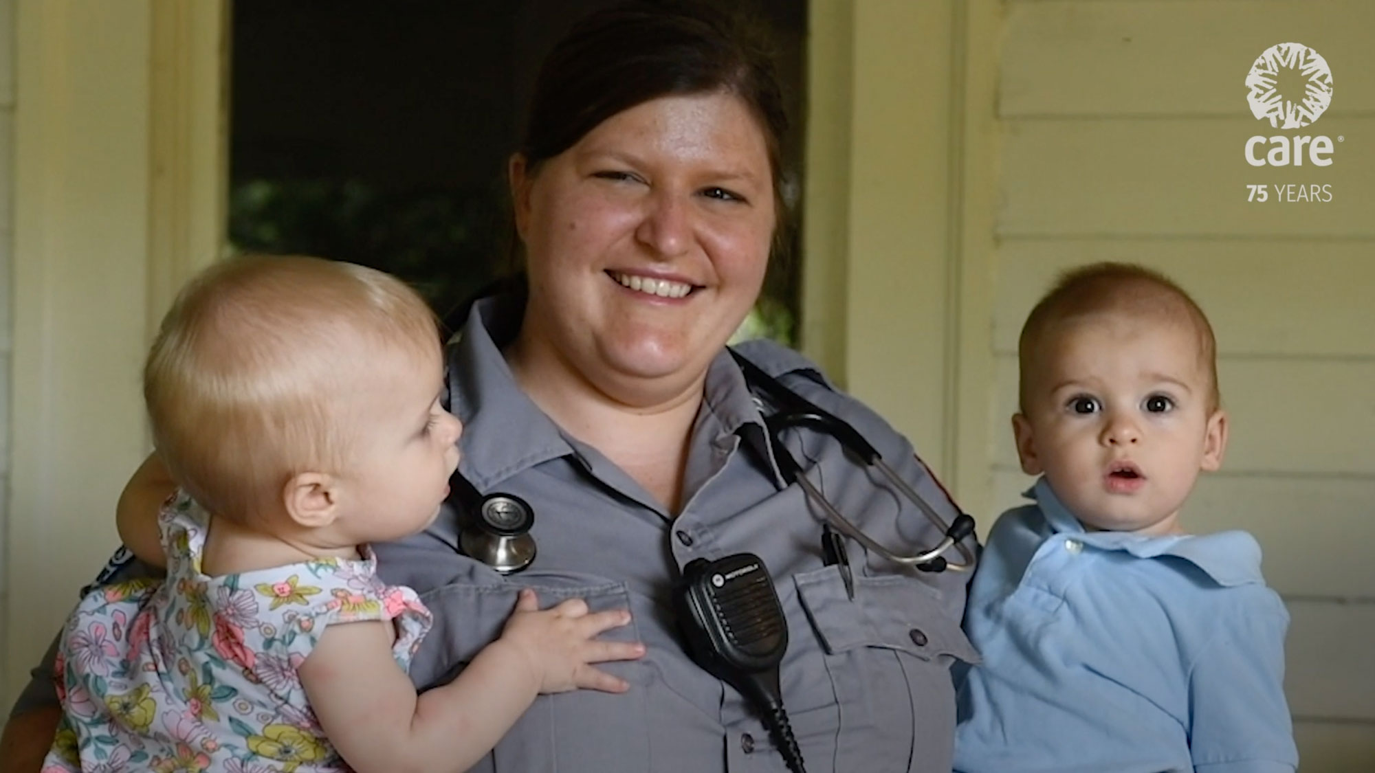 A woman paramedic smiles and hold two small children in her arms on the front porch of a house.