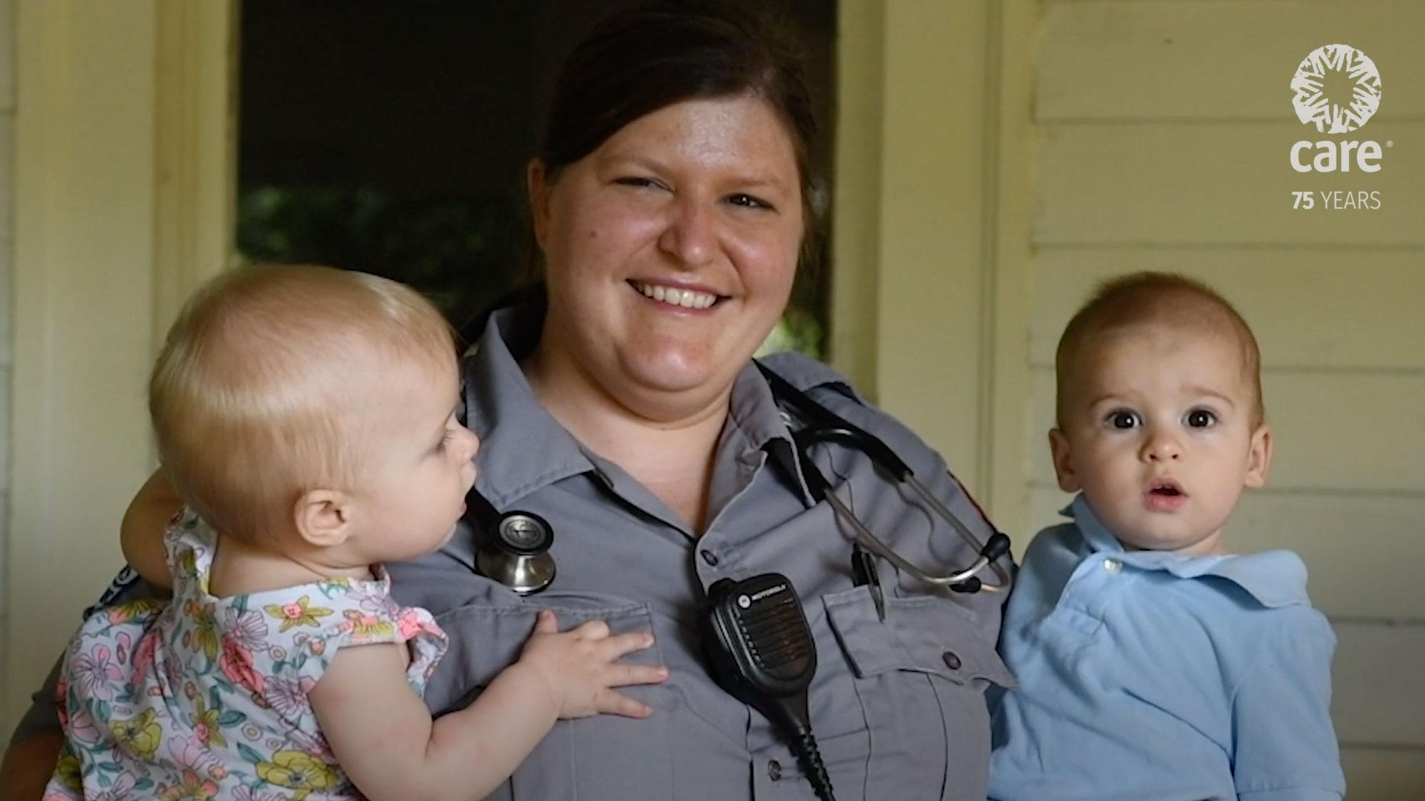 Uma paramédica sorri e segura duas crianças pequenas nos braços na varanda de uma casa.