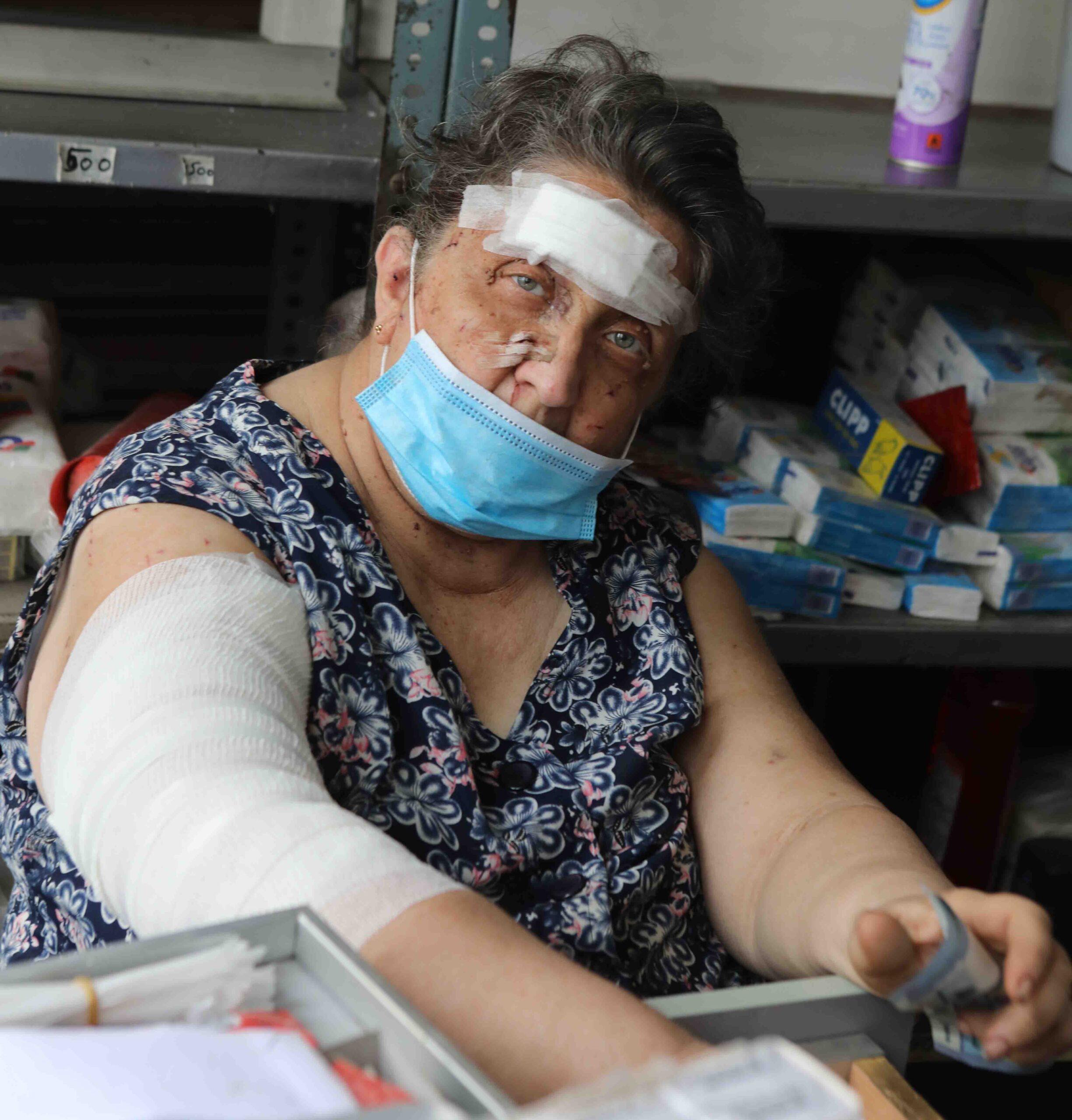 Uma mulher libanesa idosa ferida com bandagens na cabeça e no braço direito olha diretamente para a frente.