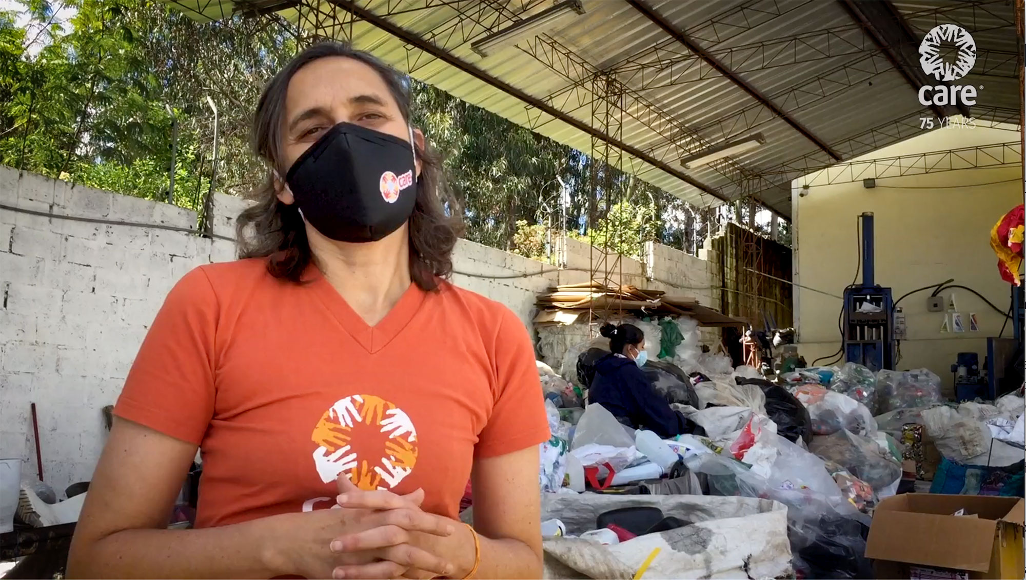 a woman in a face mask stands in front of a recycling processing plant while people in masks work behind her.