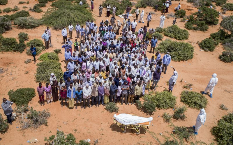 In this April 30, 2020, file photo, mourners gather to bury an elderly man believed to have died of the coronavirus but whose family asked not to be named because of the social stigma, in Mogadishu, Somalia. A dangerous stigma has sprung up around the coronavirus in Africa — fueled, in part, by severe quarantine rules in some countries as well as insufficient information about the virus. (AP Photo/File)