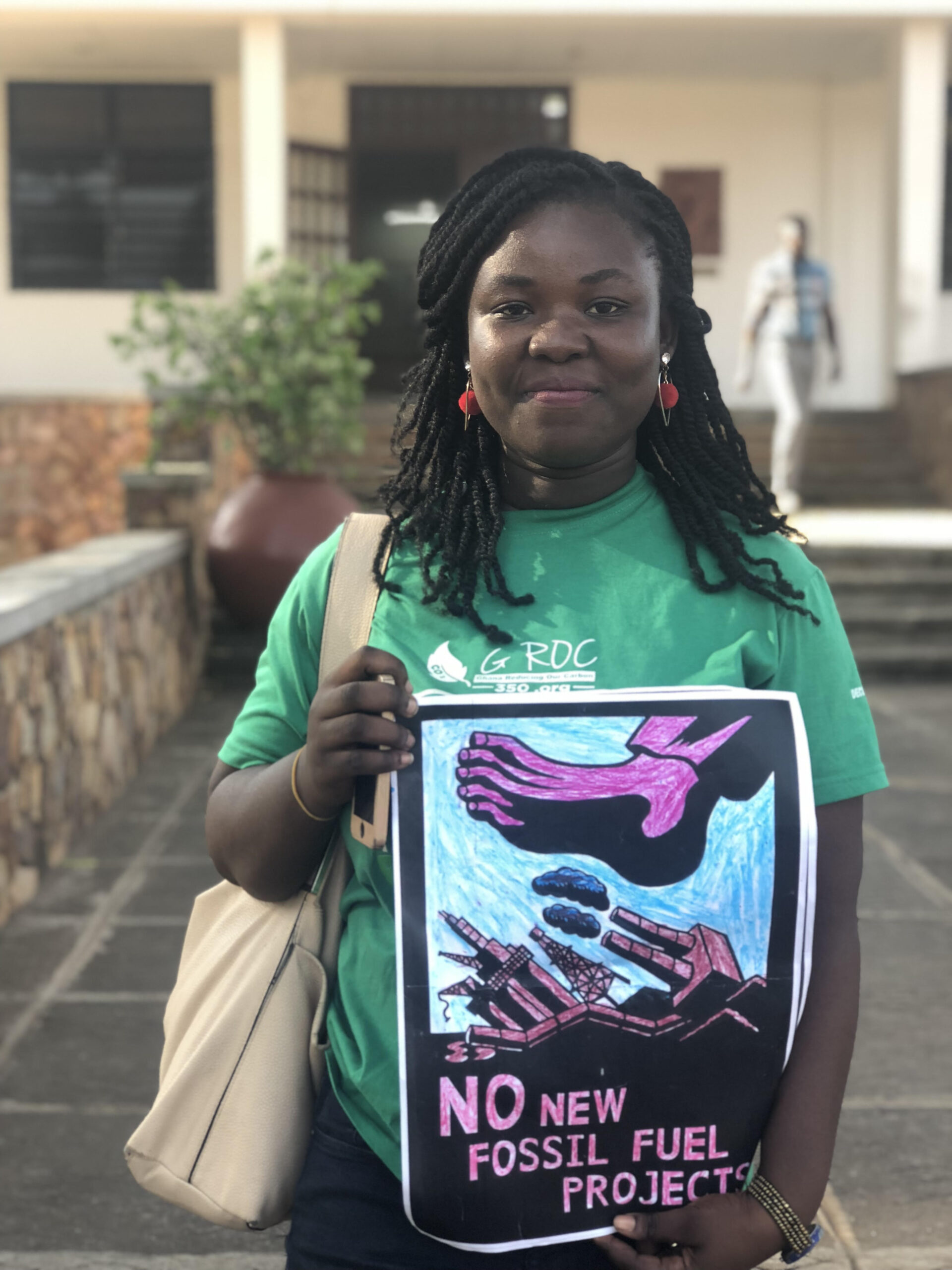 A young woman climate activist looks forward with a cloth bag on her shoulder.