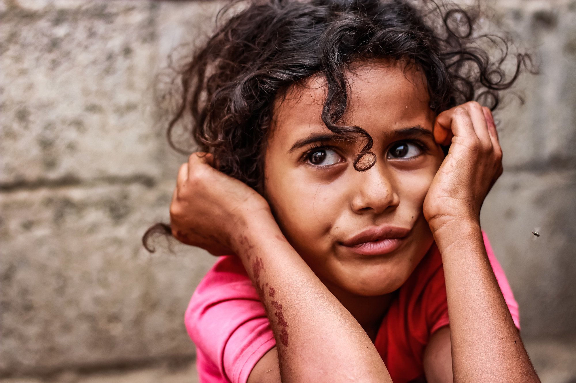 A young girl holds her head in her hands with a sad expression on her face.