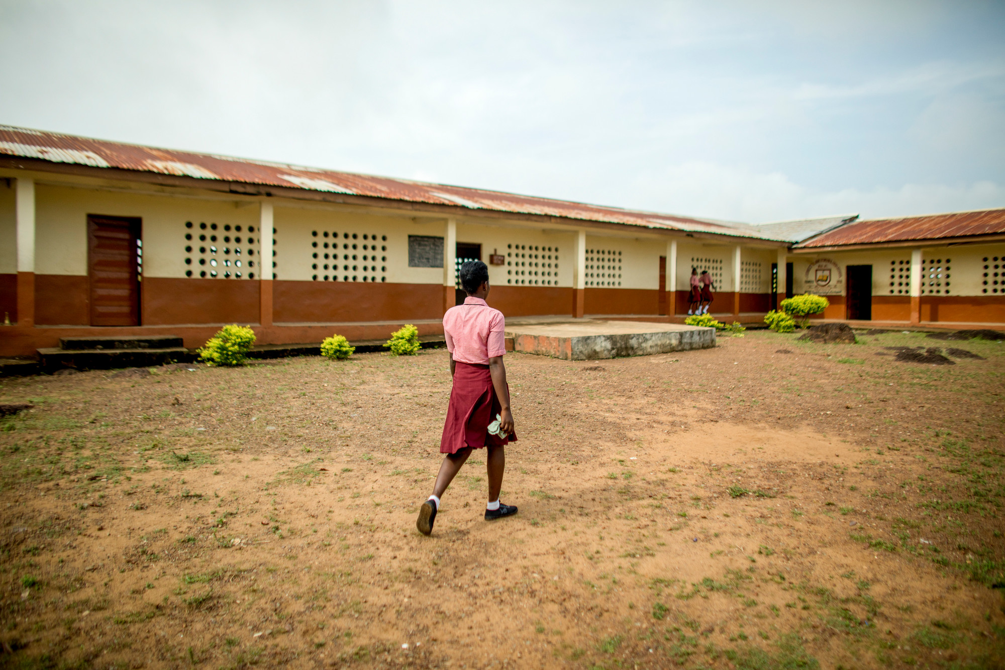 A girl walks in the dirt courtyard of a school in Sierra Leone.