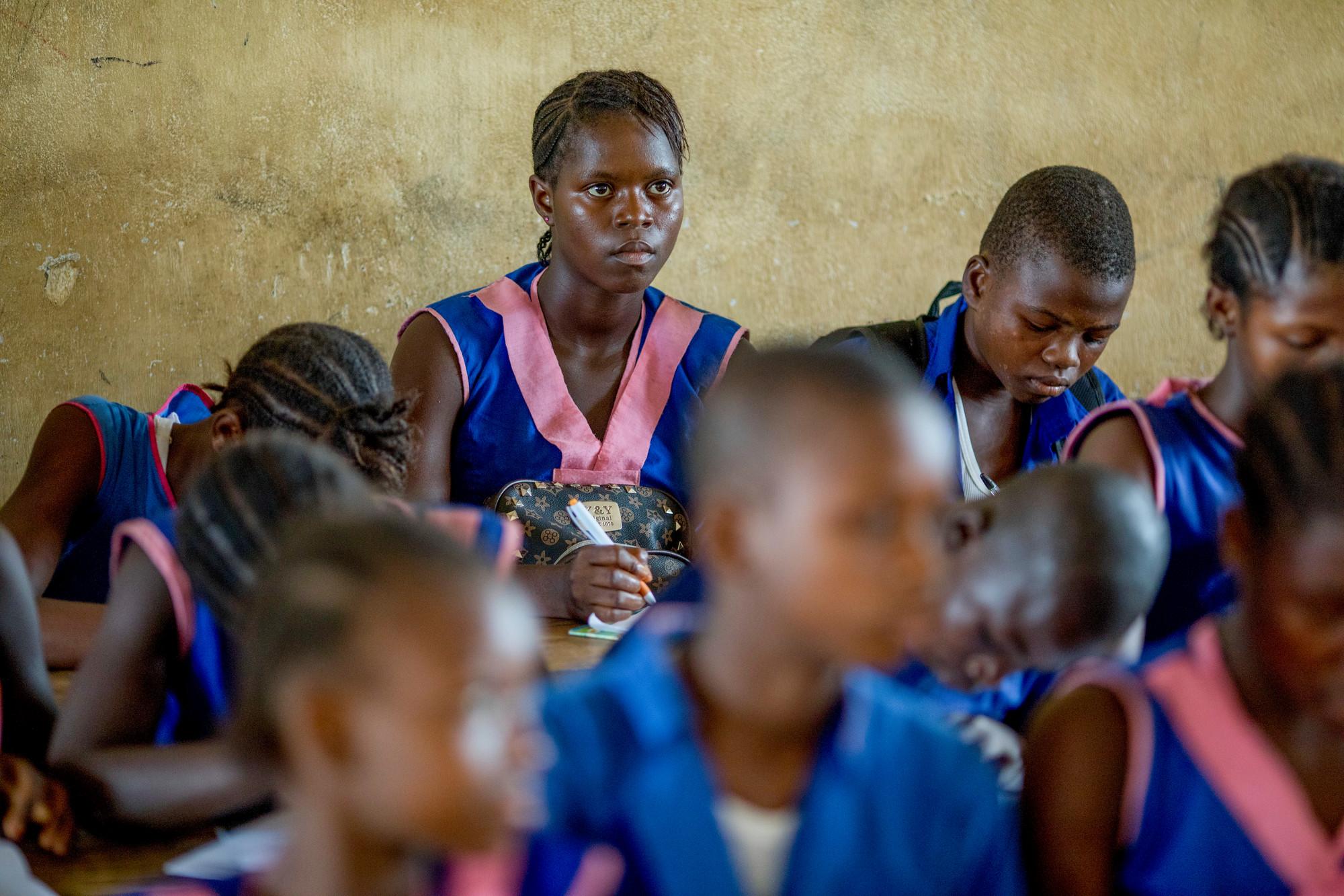 Uma garota em uma sala de aula olha para a frente cercada por outros alunos.