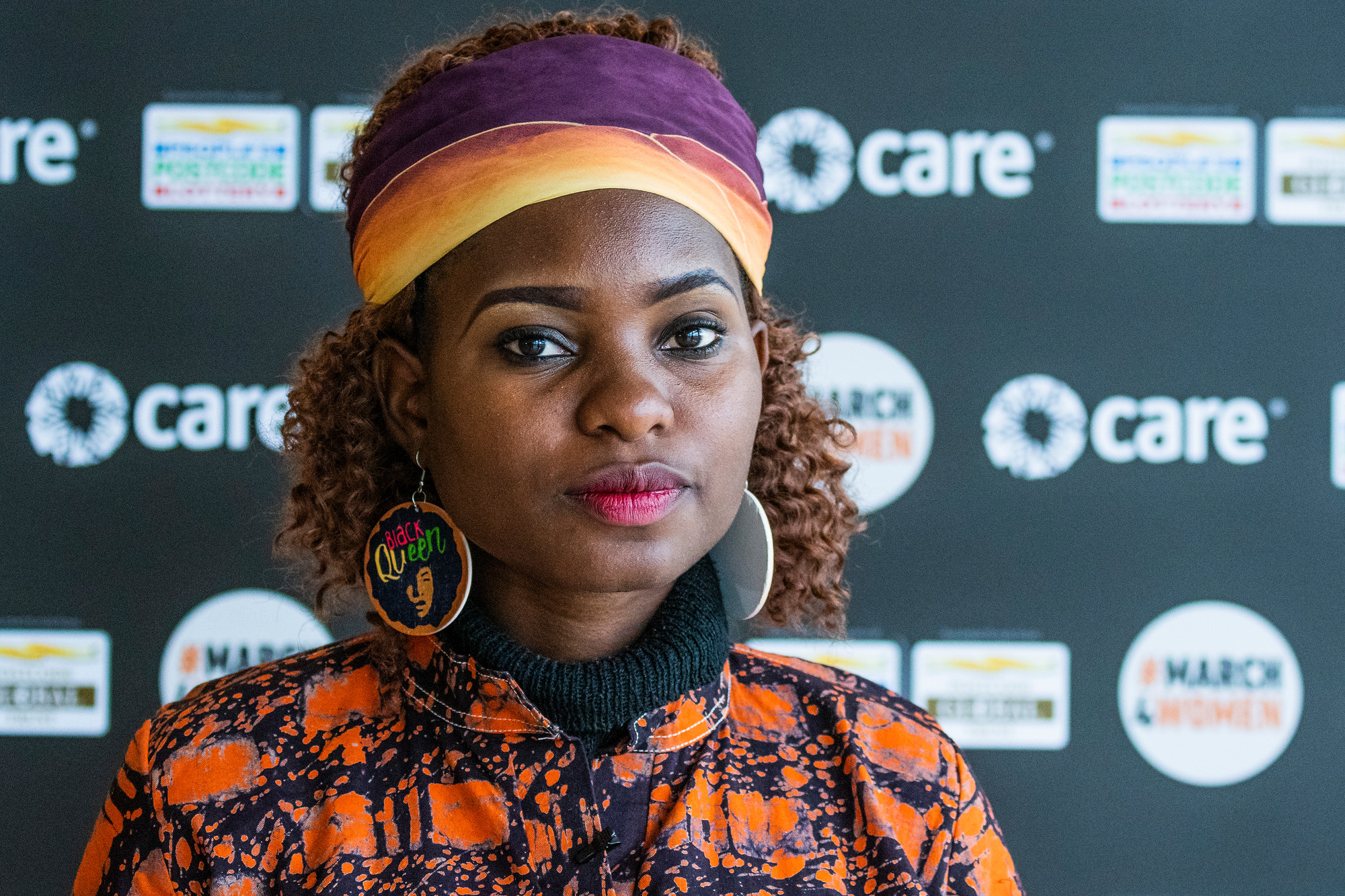 A woman climate activist in a headband stands in front of a CARE-branded backdrop