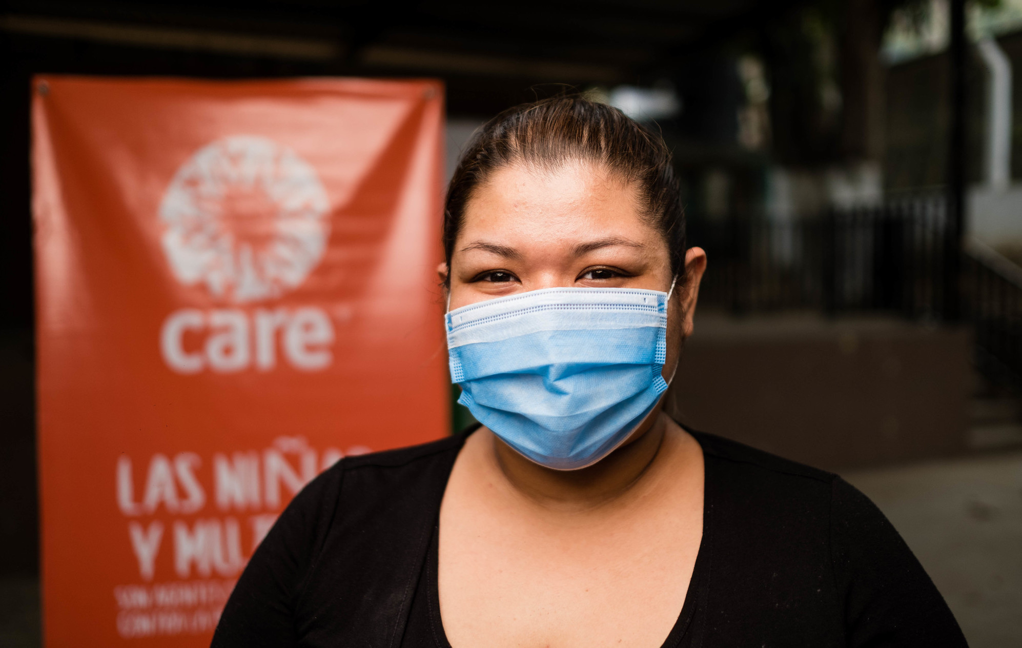 A woman in a mask stands in front of a CARE sign.