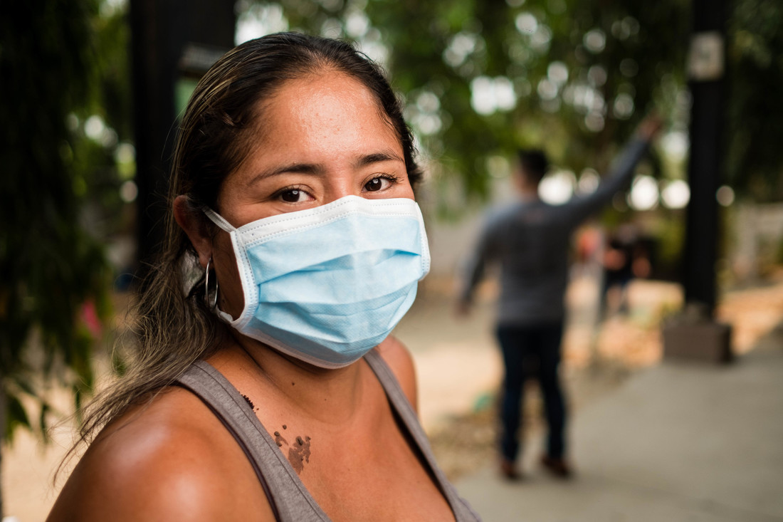 A close-up of a Honduran woman with her body facing towards the right and her face looking straight at the camera. She is wearing a light brown tank top and her dark brown eyes are visible over her light blue medical face mask.