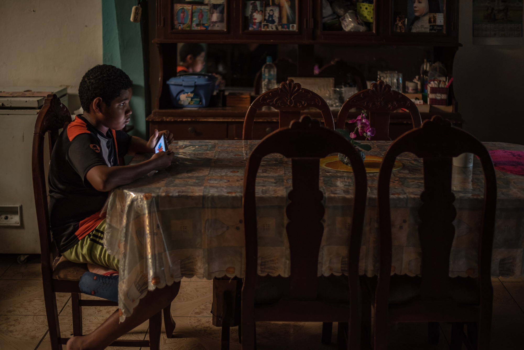 A boy sits at a table looking at a mobile phone.