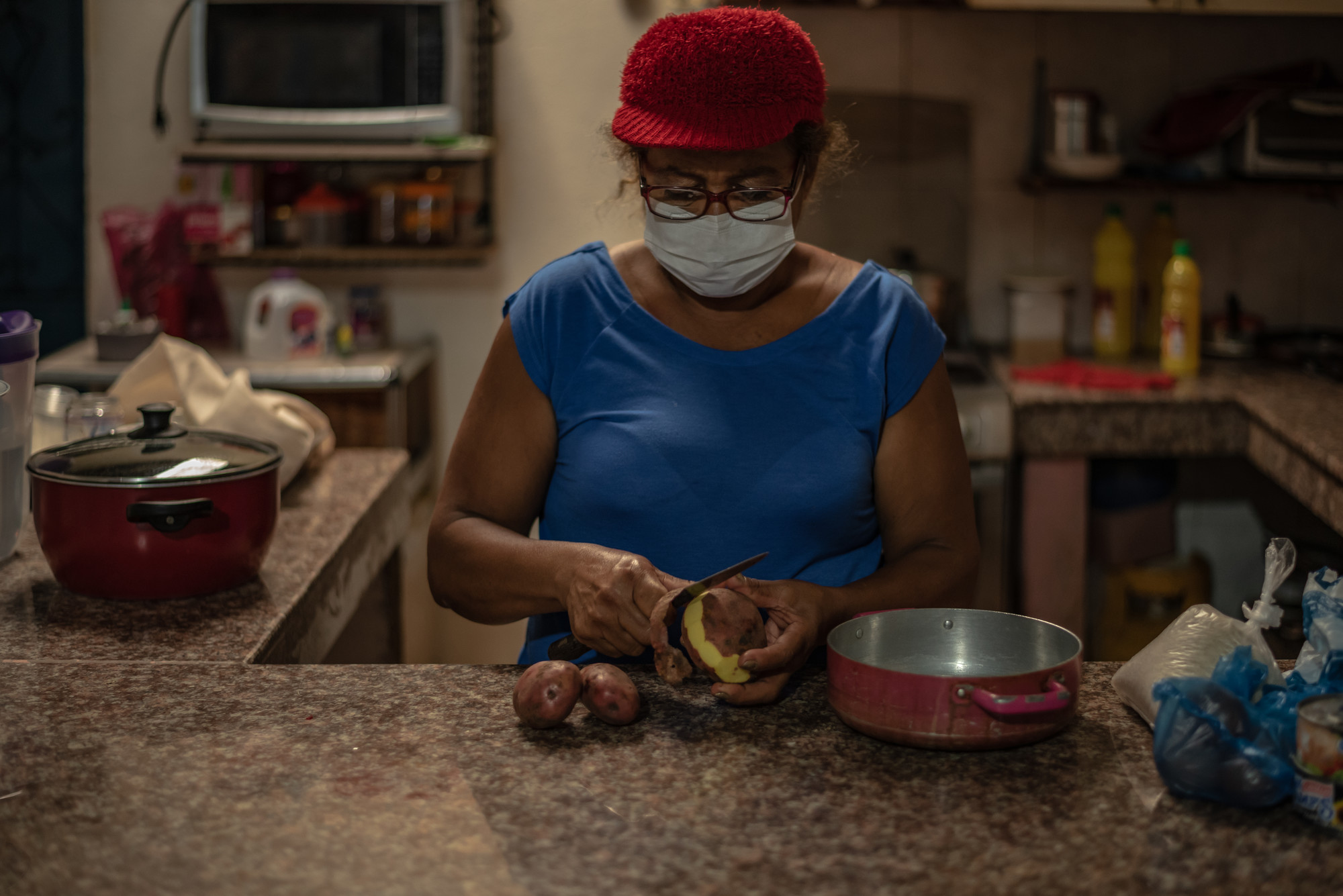 A woman in a face mask peels a potato in a kitchen.