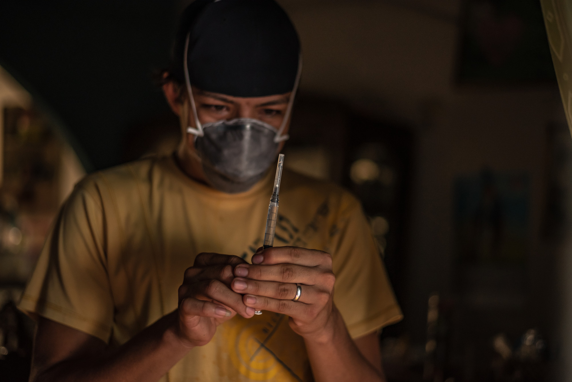 A man in a face mask looks at a syringe