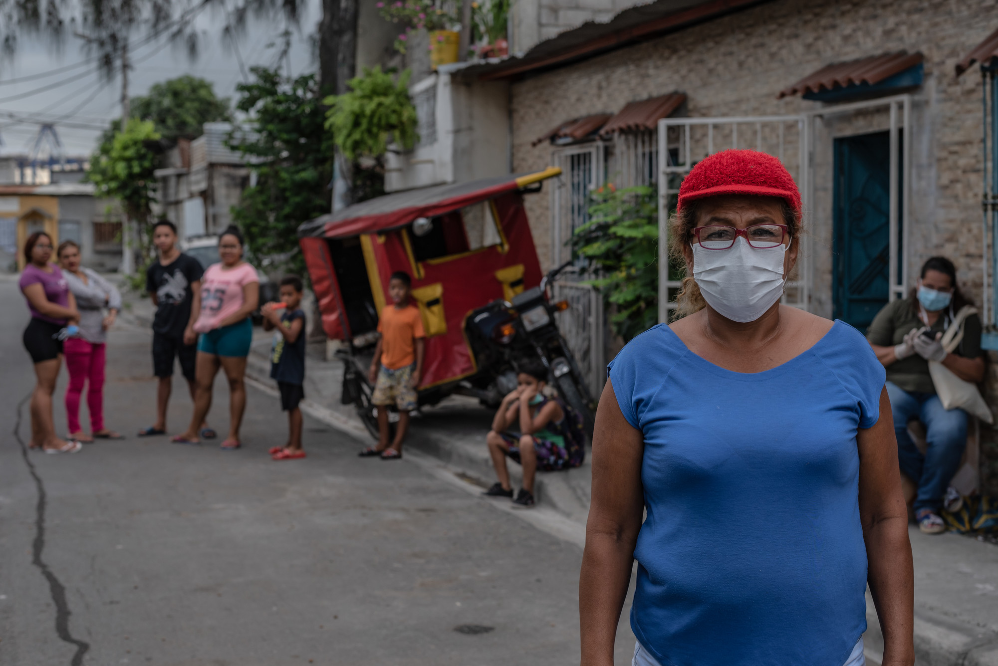 A woman in a hat and face mask stands in a city street in front of her apartment