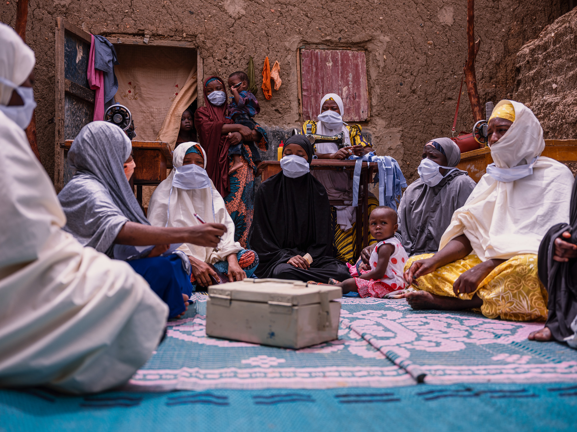 A group of women in a meeting while sitting on a rug with a money lockbox .