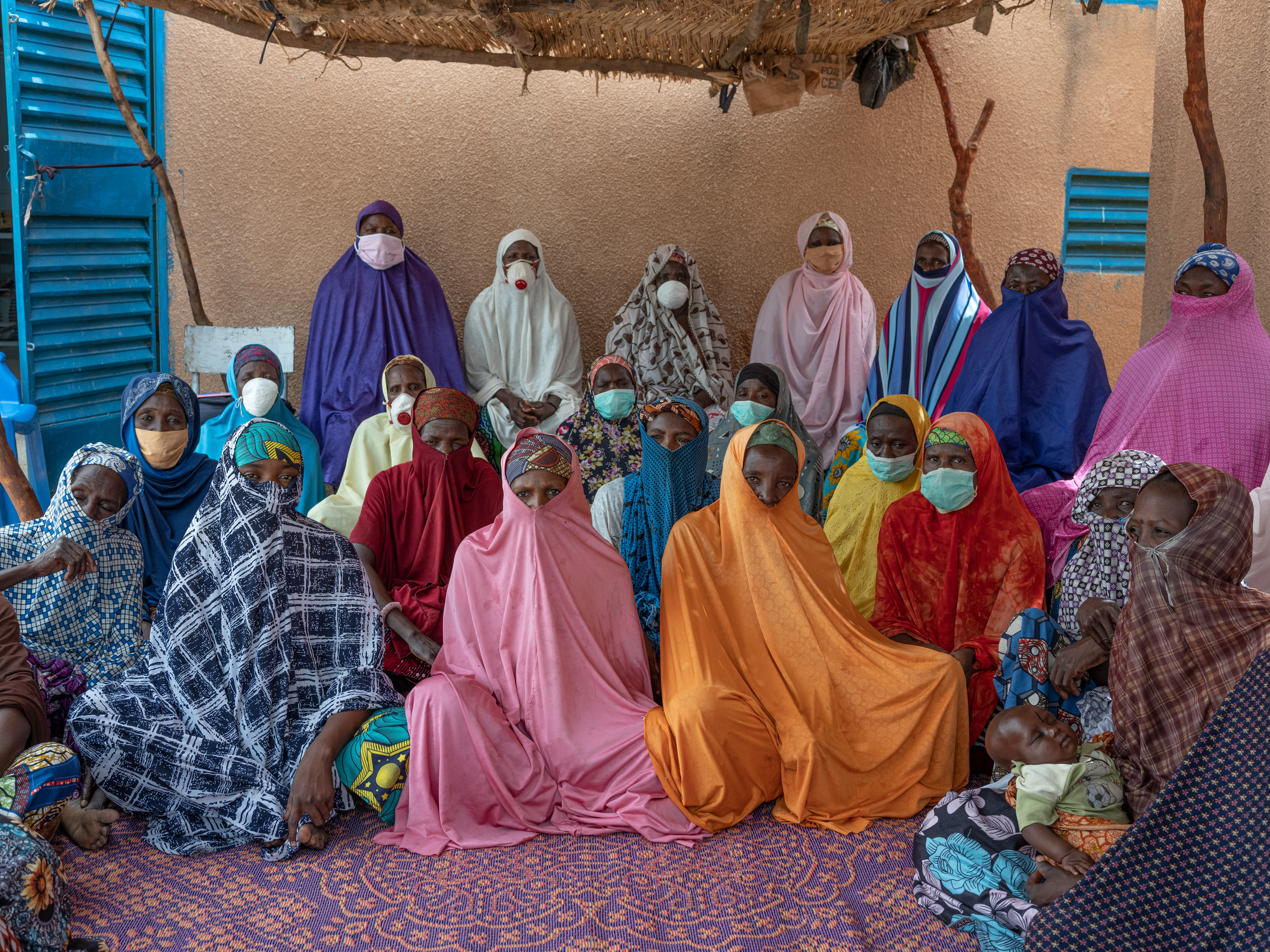 A group of women in colorful robes and face masks pose in rows facing forward.