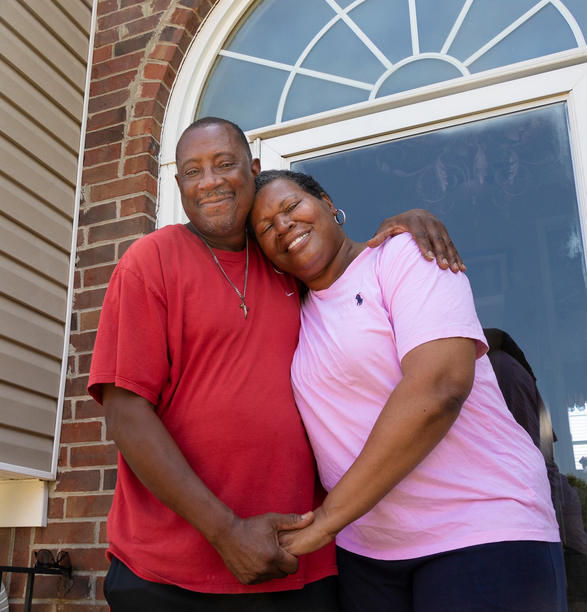 Un esposo y una esposa se toman de la mano mientras están parados en el porche de su casa frente a una puerta de vidrio.