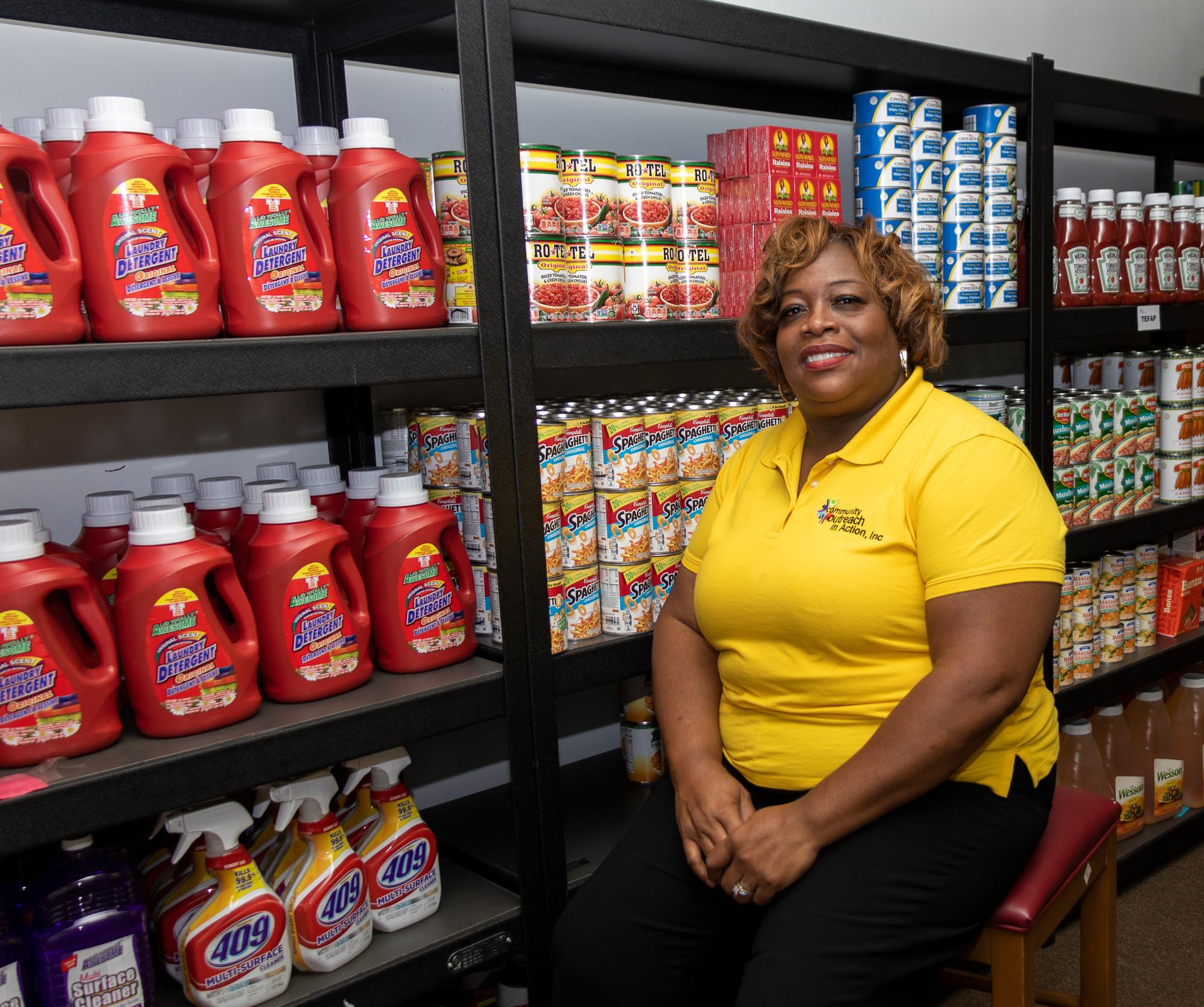 Uma gerente de um banco de alimentos está sentada em frente a prateleiras repletas de alimentos.