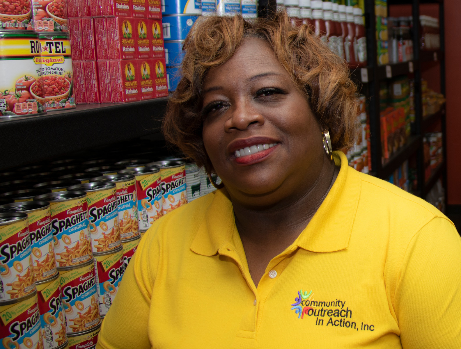 A woman manager of a food bank sits in front of shelves stocked with food items.
