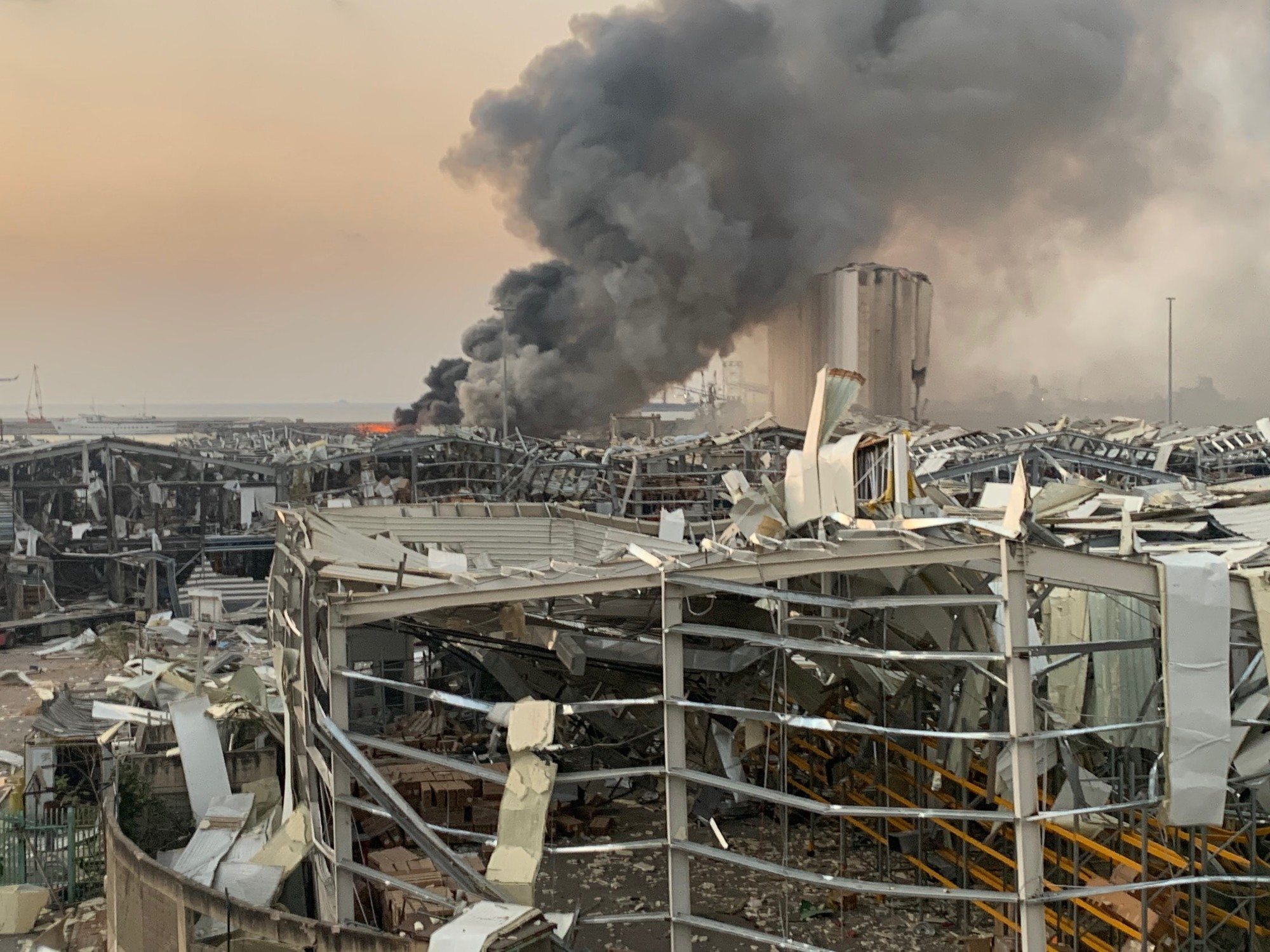 A plume of smoke rises amid the wreckage of the port in Beirut.